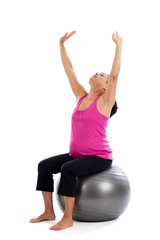Healthy Hispanic pregnant woman stretching on a fitness ball