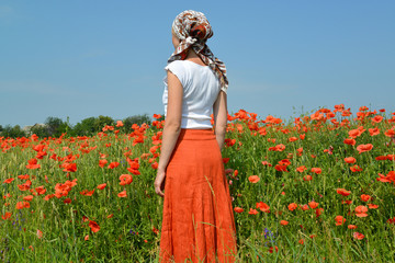 The young woman costs in a poppy field