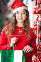 Woman In Santa Hat Carrying Shopping Bag