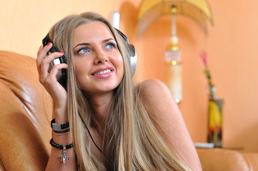 Attractive young girll listening music through headphones