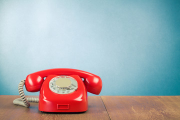 Retro red telephone on wood table near aquamarine background