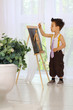 A little boy paints on an easel in the room near the window