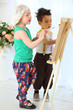 Little girl and boy paints on an easel