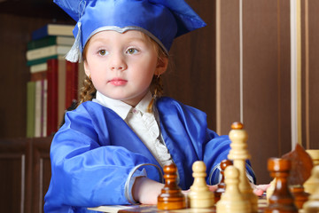 Portrait of thoughtful little girl in blue suits play chess