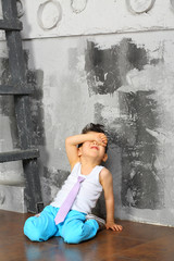 A boy sits on the floor and closes her eyes