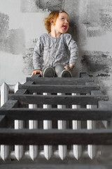 Little red-haired girl sitting on a stairs and making faces