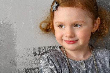 Portrait of a little red-haired girl near the gray wall