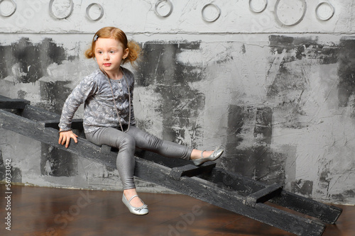 Little girl sitting on a stairs near the gray wall