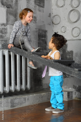 The girl sitting on a ladder and looks at the boy