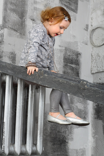 Happy little girl sitting on a ladder and looking down