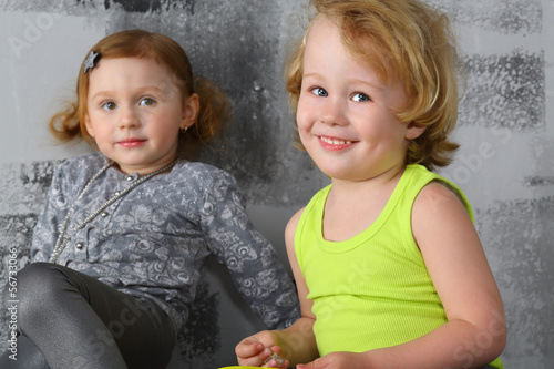 Portrait of a happy little boy with girl near the gray wall