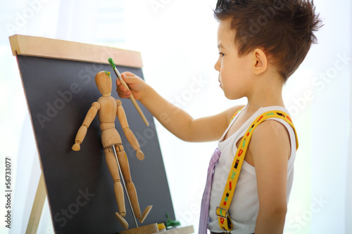 A little boy paints the wooden man near easel