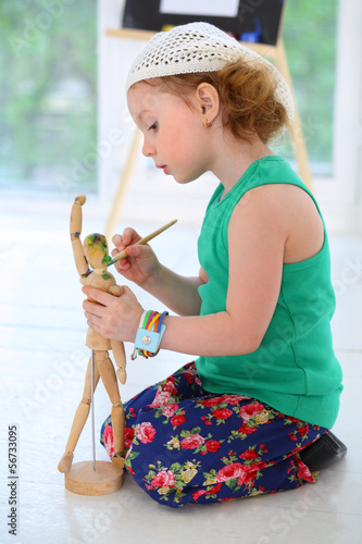 The little girl sitting on the floor and paints wooden man