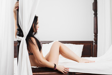 Young woman in underwear sit on the bed