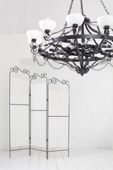 Folding screen and a black chandelier in a room