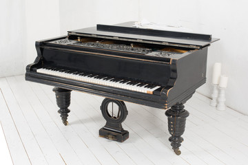 Black piano and two candles in a light room