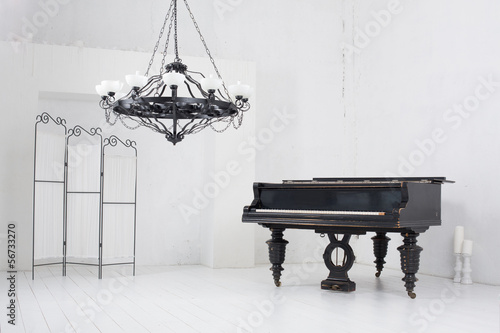 Light room with a piano, a folding screen and a chandelier