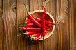 chili peppers in bowl on wooden table