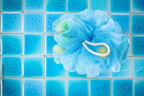 Soft blue bath puff or sponge  on blue tile  background