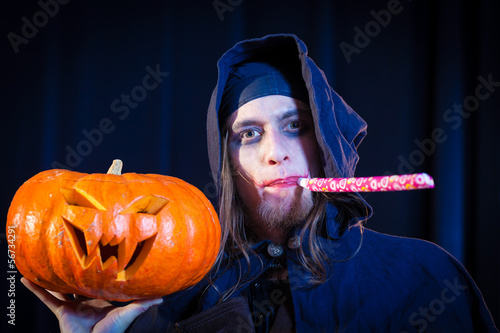 Man in scary Halloween costume holding pumpkin