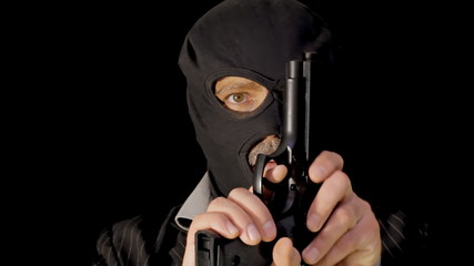 Masked criminal rising from darkness ominous with gun