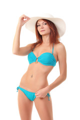 Red-haired beauty in a bikini and beach hat