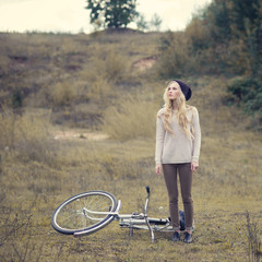 beautiful girl in a cap hipster next to a bicycle