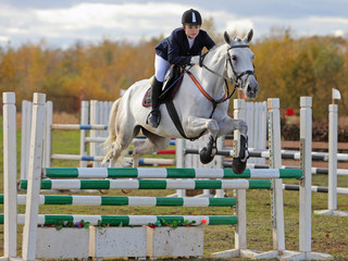 Female rider jumping over the barrier