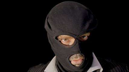 Masked criminal showing chopper knife close up