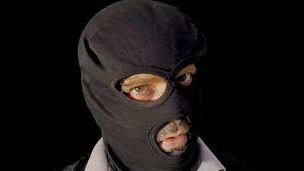 Masked criminal showing gun close up
