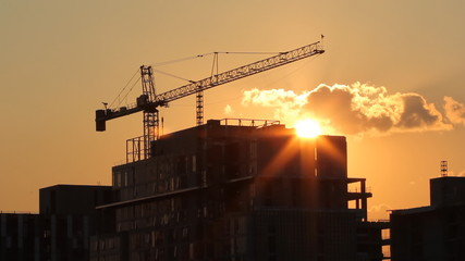 Tower crane and condominium at sunset. Real time shot.