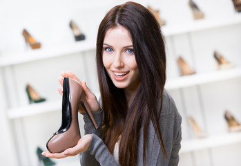 Portrait of woman keeping coffee-colored leather shoe