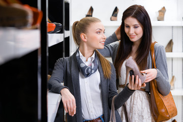Salesperson shows stylish shoes to the customer