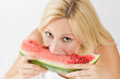 Happy young woman eating fresh watermelon