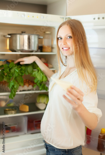 long-haired woman near opened refrigerator