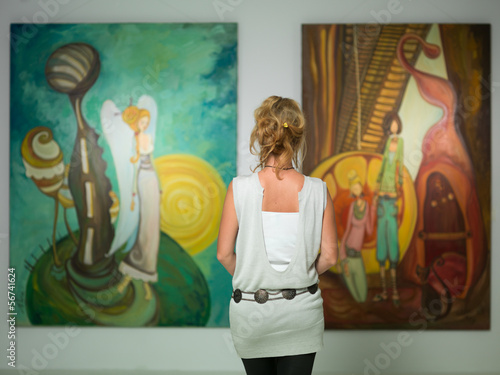Leinwanddruck Bild woman contemplating colorful paintings