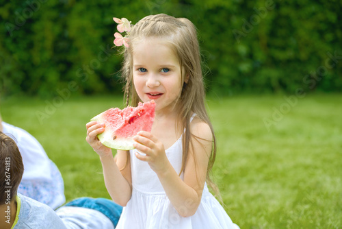Cute little girl eating red watermelon