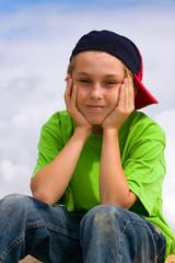 Smiling boy relaxing head in hands