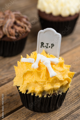 Colorful Halloween cupcakes on a rustic wooden table
