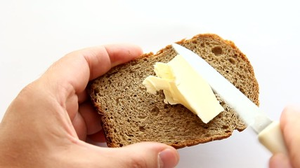 Butter being spread on a  toast slice.