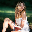 Beautiful young woman with a book under a tree in the park.