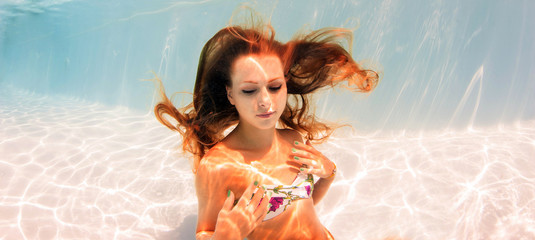 Underwater woman portrait in swimming pool.