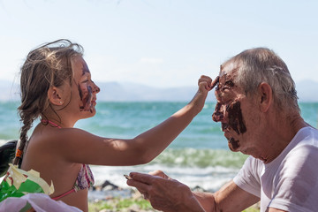 granddaughter grandfather smears face with mud