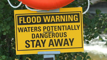 Flood warning sign with river in background.