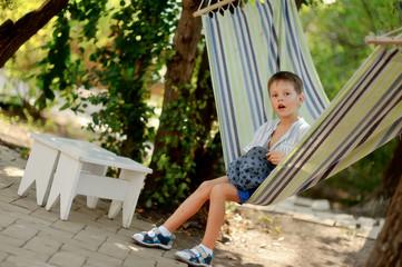 in the park cute little boy swinging in a hammock