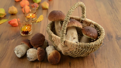 Basket with penny bun mushrooms with autumn decoration.