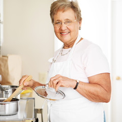 happy grandmother cooking in kitchen