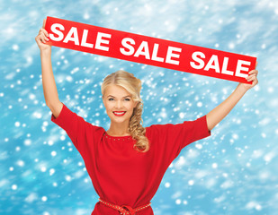 smiling woman in red dress with sale sign