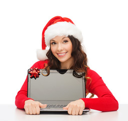 woman in santa helper hat with laptop computer