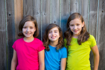 Sister and friends kid girls portrait smiling on gray fence